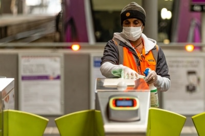 A worker wearing a mask cleans and sanitizes the ticket gates at Southern Cross Station due to COVID 19 on 12 April, 2020 in Melbourne, Australia. (Photo by Speed Media/Icon Sportswire)