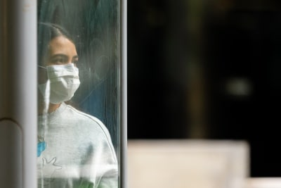 Melbourne, Australia, 12 April, 2020. A woman wearing a facemask waits for a tram during the  COVID-19 Crisis in Melbourne, Phillip Island Circuit, Australia. Credit: Dave Hewison/Alamy Live News