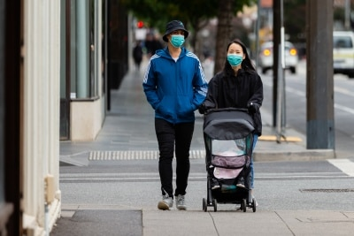 A couple walk down Chapel Street wearing masks during  COVID 19 on 12 April, 2020 in Melbourne, Australia. (Photo by Speed Media/Icon Sportswire)