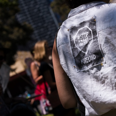 """A woman wears a """"Stop Adani"""" patch on her back during an Extinction Rebellion protest in Melbourne.  A small group of climate protesters marched from Flagstaff Gardens to The Queen Victoria Market and ending with two individuals gluing themselves together, and then glued themselves to Victoria Avenue outside of the Market. This comes as 5 new COVID-19 cases were uncovered in Melbourne's revamped Hotel Quarantine, breaking almost 40 days of virus free days."""