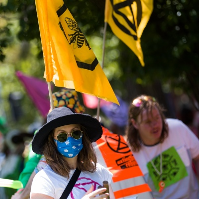 A protester wearing a mask is seen with flags behind her during an Extinction Rebellion protest in Melbourne.  A small group of climate protesters marched from Flagstaff Gardens to The Queen Victoria Market and ending with two individuals gluing themselves together, and then glued themselves to Victoria Avenue outside of the Market. This comes as 5 new COVID-19 cases were uncovered in Melbourne's revamped Hotel Quarantine, breaking almost 40 days of virus free days.