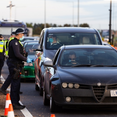 """Police are seen checking drivers reason for travel at the Kalkallo checkpoint during COVID-19 in Melbourne, Australia.  As restrictions are set to ease at Midnight tonight, the State Government have significantly amped up their """"Ring of Steel"""" metropolitan border checkpoints promising that anyone travelling out of Melbourne to regional areas will be checked and turned back if not travelling for lawful reasons. Penalties have increased to close to $5,000 for Melbournians who illegally travel to Regional Victoria."""