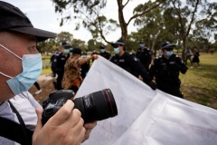 MELBOURNE, VIC - SEPTEMBER 19: Police detain a protester with a banner as press photographers shoot the chaos during the Freedom protest on September 19, 2020 in Melbourne, Australia. Freedom protests are being held in Melbourne every Saturday and Sunday in response to the governments COVID-19 restrictions and continuing removal of liberties despite new cases being on the decline. Victoria recorded a further 21 new cases overnight along with 7 deaths. (Photo by Speed Media/Icon Sportswire)