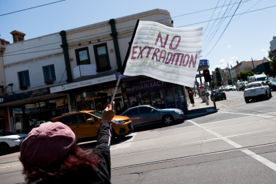 """Melbourne, Australia, 20 December, 2020. A woman holds up a 'No Extradition"""" flag during the Bring Julian Assange Home Rally on December 20, 2020 in Melbourne, Australia. On 4 January, a British judge is set to rule on whether Julian Assange should be extradited to the United States, where he could face a 175-year sentence in a high-security """"supermax"""" prison. Credit: Dave Hewison/Alamy Live News"""
