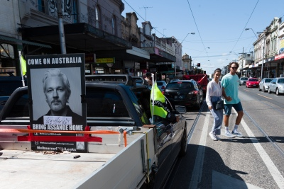 """Melbourne, Australia, 20 December, 2020. Locals are seen looking on during the Bring Julian Assange Home Rally on December 20, 2020 in Melbourne, Australia. On 4 January, a British judge is set to rule on whether Julian Assange should be extradited to the United States, where he could face a 175-year sentence in a high-security """"supermax"""" prison. Credit: Dave Hewison/Alamy Live News"""
