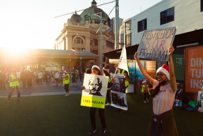 """Melbourne, Australia, 20 December, 2020. Protesters sign and dance as they hold up flags during the Bring Julian Assange Home Rally on December 20, 2020 in Melbourne, Australia. On 4 January, a British judge is set to rule on whether Julian Assange should be extradited to the United States, where he could face a 175-year sentence in a high-security """"supermax"""" prison. Credit: Dave Hewison/Alamy Live News"""