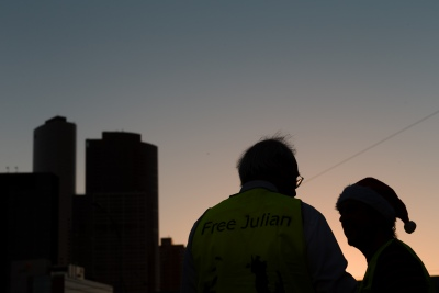 """Melbourne, Australia, 20 December, 2020. Julian Assange's father, John Shipton is seen talking to a supporter as the sun sets during the Bring Julian Assange Home Rally on December 20, 2020 in Melbourne, Australia. On 4 January, a British judge is set to rule on whether Julian Assange should be extradited to the United States, where he could face a 175-year sentence in a high-security """"supermax"""" prison. Credit: Dave Hewison/Alamy Live News"""