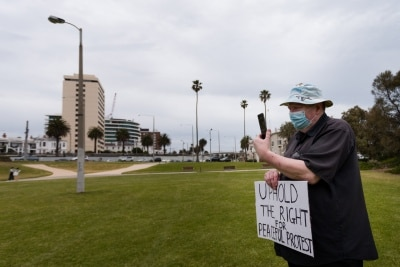 A man stands with a placard during a silent liberty protest held as a response to the excessive action Victoria Police have taken against public protests during COVID-19 in St Kilda.  With 21 days of zero new cases, Premier Daniel Andrews is expected to announce major easing of restrictions, including masks, at his press conference on Sunday.