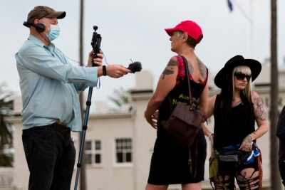 Protesters are seen being interviewed during a silent liberty protest held as a response to the excessive action Victoria Police have taken against public protests during COVID-19 in St Kilda.  With 21 days of zero new cases, Premier Daniel Andrews is expected to announce major easing of restrictions, including masks, at his press conference on Sunday.