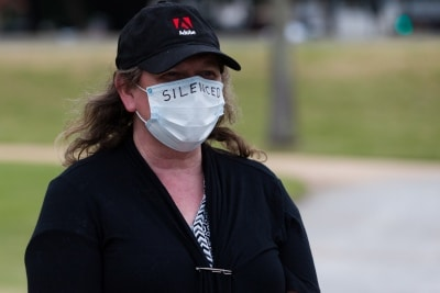 A protester wears a mask with the word 'silenced' written across it during a silent liberty protest held as a response to the excessive action Victoria Police have taken against public protests during COVID-19 in St Kilda.  With 21 days of zero new cases, Premier Daniel Andrews is expected to announce major easing of restrictions, including masks, at his press conference on Sunday.