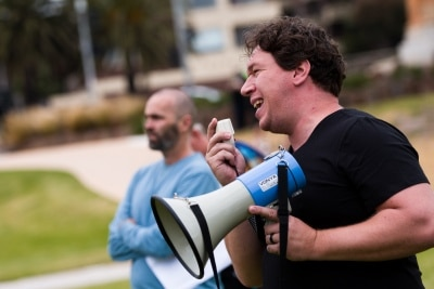 Well known libertarian Topher Field is seen speaking during a silent liberty protest held as a response to the excessive action Victoria Police have taken against public protests during COVID-19 in St Kilda.  With 21 days of zero new cases, Premier Daniel Andrews is expected to announce major easing of restrictions, including masks, at his press conference on Sunday.
