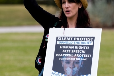 A protester holding a placard cheers as speakers address protesters during a silent liberty protest held as a response to the excessive action Victoria Police have taken against public protests during COVID-19 in St Kilda.  With 21 days of zero new cases, Premier Daniel Andrews is expected to announce major easing of restrictions, including masks, at his press conference on Sunday.