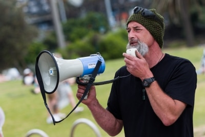 A man speaks to the protester's during a silent liberty protest held as a response to the excessive action Victoria Police have taken against public protests during COVID-19 in St Kilda.  With 21 days of zero new cases, Premier Daniel Andrews is expected to announce major easing of restrictions, including masks, at his press conference on Sunday.