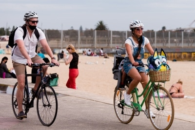 A woman rides her bike along St Kilda Beach during the final days of the worlds toughest and longest COVID-19 restrictions in St Kilda.  With 21 days of zero new cases, Premier Daniel Andrews is expected to announce major easing of restrictions, including masks, at his press conference on Sunday.