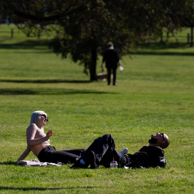 A couple is seen laughing in the park during COVID-19 in Melbourne, Australia. Victoria records 5 new cases and three deaths as restrictions are slightly eased. This comes just days after Health Minister Jenny Mikakos resigned over the Hotel Quarantine bungle and as pressure mounts for the Premier, Daniel Andrews, to resign. As the Spring weather sees warmer days, more Melbournians are simply ignoring the rules.