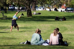 A man is seen attempting a handstand in front of a group of women in Princes Park  during COVID-19 in Melbourne, Australia. Victoria records 5 new cases and three deaths as restrictions are slightly eased. This comes just days after Health Minister Jenny Mikakos resigned over the Hotel Quarantine bungle and as pressure mounts for the Premier, Daniel Andrews, to resign. As the Spring weather sees warmer days, more Melbournians are simply ignoring the rules.