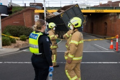 Fire crews wait for a truck to be dislodged from the Albert Street Bridge on Monday evening. A truck has hit an overhead rail bridge on Albert Road , Albert Park resulting in emergency services arriving at the scene.