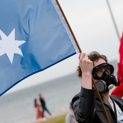 A man wearing a gas mask is seen holding  a flag during the Sack Daniel Andrews Protest in St Kilda. Parts of the community are looking to hold the Victorian Premier accountable for the failings of his government that led to more than 800 deaths during the Coronavirus crisis. Victoria has recorded 36 days Covid free as pressure mounts on the Premier Daniel Andrews to relax all remaining restrictions.