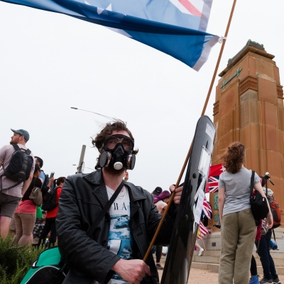 A man in a gas mask holds up a mock flag during the Sack Daniel Andrews Protest in Fawkner Park. Parts of the community are looking to hold the Victorian Premier accountable for the failings of his government that led to more than 800 deaths during the Coronavirus crisis. Victoria has recorded 36 days Covid free as pressure mounts on the Premier Daniel Andrews to relax all remaining restrictions.