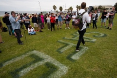 """Protesters gather around the """"Play it Safe"""" sign painted on the grass in St Kilda during the Sack Daniel Andrews Protest in St Kilda. Parts of the community are looking to hold the Victorian Premier accountable for the failings of his government that led to more than 800 deaths during the Coronavirus crisis. Victoria has recorded 36 days Covid free as pressure mounts on the Premier Daniel Andrews to relax all remaining restrictions."""