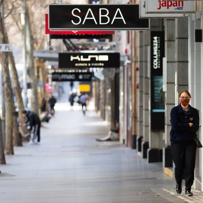 A view of Collins Street as a woman wearing a facemask takes a walk and a small number of people are seen in the background during COVID-19 in Melbourne, Australia. Stage 4 restrictions continue in Melbourne as work permits come into effect at midnight today. This comes as a further 471 new COVID-19 cases were uncovered overnight.