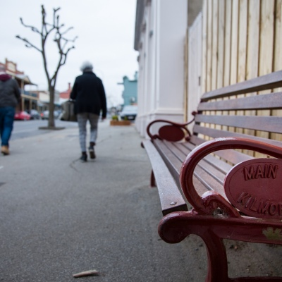 """A street bench is seen with """"Main Street Kilmore"""" written on its side as locals walk by during COVID-19 in Kilmore, Australia. An outbreak which started in Chadstone in Melbourne, has spread as far as Benalla. Twenty-eight people linked to the outbreak have now tested positive for COVID-19. There are now two confirmed cases in Kilmore linked with a Melbourne Resident who carried the virus into the town. The person visited the Odd Fellows Cafe in Kilmore which lead to him spreading the virus to a staff member, and a customer. The cafe has been closed for deep cleaning and will remain closed until the 19th October."""