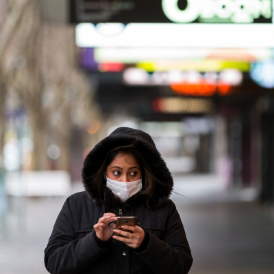 A woman wearing a facemask holds her phone as she walks along along Collins Street during peak hour during COVID-19 in Melbourne, Australia. Stage 4 restrictions continue in Melbourne as life drains away from the city now that work permits are being enforced. Premier Daniel Andrews once again failed to answer questions on his administrations failures that led to over 180 deaths in his state. Victoria recorded a further 450 new COVID-19 infections along with 11 deaths overnight.