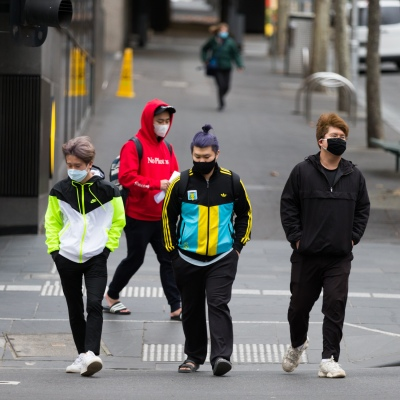 Melbournians wearing masks walk across a crossing in what is usually peak hour during COVID-19 in Melbourne, Australia. Stage 4 restrictions continue in Melbourne as life drains away from the city now that work permits are being enforced. Premier Daniel Andrews once again failed to answer questions on his administrations failures that led to over 180 deaths in his state. Victoria recorded a further 450 new COVID-19 infections along with 11 deaths overnight.