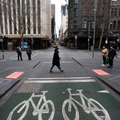 A woman wearing a mask is seen crossing an empty intersection during peak hour during COVID-19 in Melbourne, Australia. Stage 4 restrictions continue in Melbourne as life drains away from the city now that work permits are being enforced. Premier Daniel Andrews once again failed to answer questions on his administrations failures that led to over 180 deaths in his state. Victoria recorded a further 450 new COVID-19 infections along with 11 deaths overnight.
