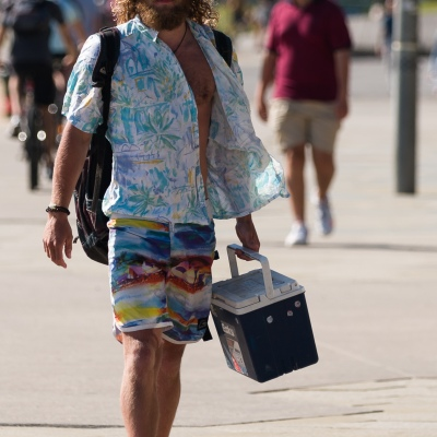 A man wearing a yellow hat and carrying an esky is seen walking during COVID-19 in St Kilda Beach, Australia. Despite desperate attempts by the Premier to renew his COVID fear, thousands of Melbournians enjoy the sun at St Kilda Beach. A total of only 39 active cases currently exist in Victoria, despite this, Victorians currently in Queensland and NSW are being prevented from coming home. Zero new cases were discovered in Victoria today.  during COVID-19 in Victoria, Australia. Despite desperate attempts by the Premier to renew his COVID fear, thousands of Melbournians enjoy the sun at St Kilda Beach. A total of only 39 active cases currently exist in Victoria, despite this, Victorians currently in Queensland and NSW are being prevented from coming home. Zero new cases were discovered in Victoria today.