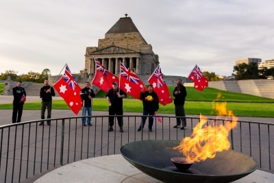 MELBOURNE, AUSTRALIA - APRIL 25: Members of the Australian Sovereign Counsel stand holding Australia's Red Ensign in front of the Shrine of Remembrance with the Eternal Flame in the foreground shortly after the dawn service during COVID 19 on ANZAC Day 25 April, 2020 in Melbourne, Australia. (Photo by Speed Media/Icon Sportswire)