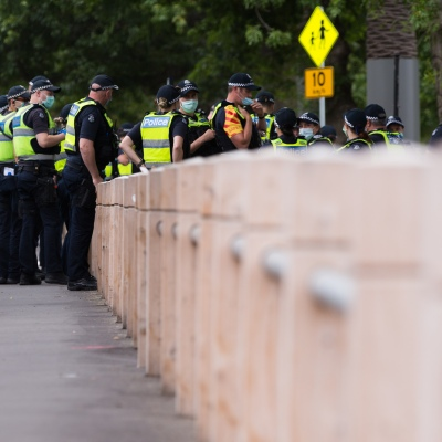 Large numbers of Police are seen during a protest in response to mandatory COVID-19 vaccinations at Fawkner Park on February 20, 2021 in Melbourne, Victoria Australia. Up to 680,000 people are set to receive the first lot of Pfizer/BioNTech vaccinations. Hotel quarantine, health hotel workers, airport and port workers, high-risk frontline health staff and public sector residential aged care staff and residents will be the first under Phase 1A of the roll-out plan.