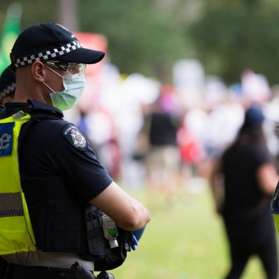 A police officer is seen as thousands of protesters walk by during a protest in response to mandatory COVID-19 vaccinations at Fawkner Park on February 20, 2021 in Melbourne, Victoria Australia. Up to 680,000 people are set to receive the first lot of Pfizer/BioNTech vaccinations. Hotel quarantine, health hotel workers, airport and port workers, high-risk frontline health staff and public sector residential aged care staff and residents will be the first under Phase 1A of the roll-out plan.