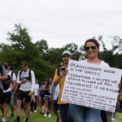A protester is seen holding up an anti media placard during a protest in response to mandatory COVID-19 vaccinations at Fawkner Park on February 20, 2021 in Melbourne, Victoria Australia. Up to 680,000 people are set to receive the first lot of Pfizer/BioNTech vaccinations. Hotel quarantine, health hotel workers, airport and port workers, high-risk frontline health staff and public sector residential aged care staff and residents will be the first under Phase 1A of the roll-out plan.