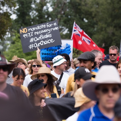 Protesters are seen holding placards during a protest in response to mandatory COVID-19 vaccinations at Fawkner Park on February 20, 2021 in Melbourne, Victoria Australia. Up to 680,000 people are set to receive the first lot of Pfizer/BioNTech vaccinations. Hotel quarantine, health hotel workers, airport and port workers, high-risk frontline health staff and public sector residential aged care staff and residents will be the first under Phase 1A of the roll-out plan.