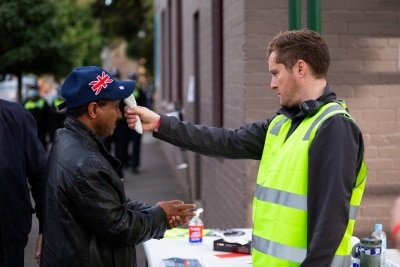 MELBOURNE, AUSTRALIA - JULY 10: A man is seen having his temperature checked before entering the main staging area outside of the remaining locked down tower at Alfred Street during COVID 19 on 10 July, 2020 in Melbourne, Australia. Former Federal Labor Leader Bill Shorten, along with close allies at Trades Hall help deliver Halal meat, supplied by Macca Halal Foods to the locked down housing commission towers following a COVID-19 outbreak detected inside the complex. Mr Shorten was able to use his high profile to ensure food was not turned away by police so that it would reach the residents inside. (Photo by Speed Media/Icon Sportswire)