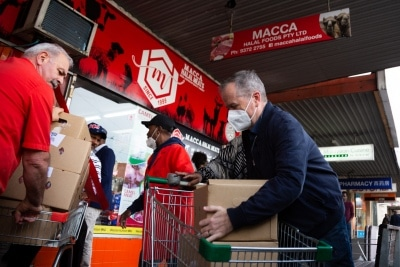 MELBOURNE, AUSTRALIA - JULY 10: Former Labor Leader Bill Shorten (R) is seen wearing a facemask as he helps load meat into a truck from Macca Halal Foods in Flemington to help feel the people affected by the housing commission tower lockdown during COVID 19 on 10 July, 2020 in Melbourne, Australia. Former Federal Labor Leader Bill Shorten, along with close allies at Trades Hall help deliver Halal meat, supplied by Macca Halal Foods to the locked down housing commission towers following a COVID-19 outbreak detected inside the complex. Mr Shorten was able to use his high profile to ensure food was not turned away by police so that it would reach the residents inside. (Photo by Speed Media/Icon Sportswire)