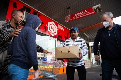 MELBOURNE, AUSTRALIA - JULY 10: Former Labor Leader Bill Shorten (R) is seen wearing a facemask as he helps locals load meat into a truck from Macca Halal Foods in Flemington to help feel the people affected by the housing commission tower lockdown during COVID 19 on 10 July, 2020 in Melbourne, Australia. Former Federal Labor Leader Bill Shorten, along with close allies at Trades Hall help deliver Halal meat, supplied by Macca Halal Foods to the locked down housing commission towers following a COVID-19 outbreak detected inside the complex. Mr Shorten was able to use his high profile to ensure food was not turned away by police so that it would reach the residents inside. (Photo by Speed Media/Icon Sportswire)