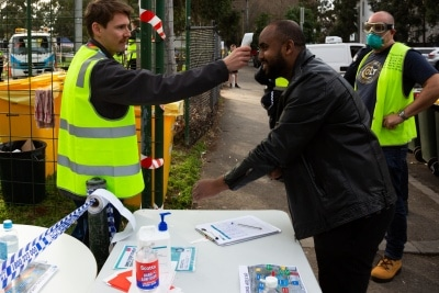 MELBOURNE, AUSTRALIA - JULY 10: Islamic Council of Victoria and Tower resident, Mukhtar Mohammed (centre) has his temperature checked before entering the staging area outside of the Alfred Street tower which is still locked down before unloading a truck full of halal meats supplied by Trades Hall to feed vulnerable residents during COVID 19 on 10 July, 2020 in Melbourne, Australia. Former Federal Labor Leader Bill Shorten, along with close allies at Trades Hall help deliver Halal meat, supplied by Macca Halal Foods to the locked down housing commission towers following a COVID-19 outbreak detected inside the complex. Mr Shorten was able to use his high profile to ensure food was not turned away by police so that it would reach the residents inside. (Photo by Speed Media/Icon Sportswire)