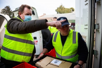 MELBOURNE, AUSTRALIA - JULY 10: Victorian Trades Hall Council Secretary, Luke Hilakari (left) is seen helping a sheriff (right) unload a delivery of meat for the residents in the Alfred Street housing commission tower during COVID 19 on 10 July, 2020 in Melbourne, Australia. Former Federal Labor Leader Bill Shorten, along with close allies at Trades Hall help deliver Halal meat, supplied by Macca Halal Foods to the locked down housing commission towers following a COVID-19 outbreak detected inside the complex. Mr Shorten was able to use his high profile to ensure food was not turned away by police so that it would reach the residents inside. (Photo by Speed Media/Icon Sportswire)