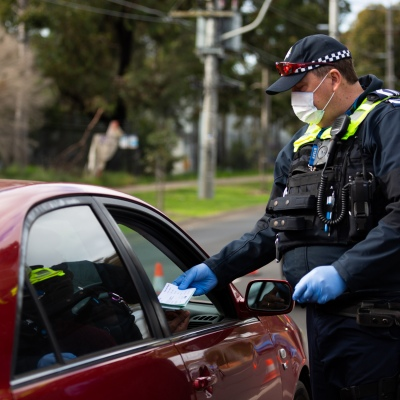 MELBOURNE, AUSTRALIA - JULY 2: Police Officers check reasons for not being at home in a booze bus style random checkpoint on Camp Road Broadmeadows entering Fawkner during COVID 19 on 2 July, 2020 in Melbourne, Australia. Stage 3 lockdowns have once again been reinstated across 36 Melbourne Suburbs at midnight today after Daniel Andrews announced on the 30th June that Coronavirus cases had spiked following a testing blitz in the affected suburbs. Overnight, and additional 77 cases were uncovered from a total of 26,000 tests. Residents can only leave their home for four reasons; Shopping for food or supplies, care and care giving, exercise and study or work. Anyone caught flouting the rules will be slapped with a $1,652 fine while business could be fined $10,000. Under Victoria's State of Emergency powers, which have once again been extended to the 19th July, police have unprecedented powers to enforce lockdown laws for both residents as well as visitors entering the 'no-go' zones. This comes despite the positive rate of testing remaining stable at 0.3% indicating that the recent spike is more a function of extra testing, rather than an increase in viral spread. The new restrictions will remain in place for four weeks and will extend to the whole state if the situation does not improve. (Photo by Speed Media/Icon Sportswire)