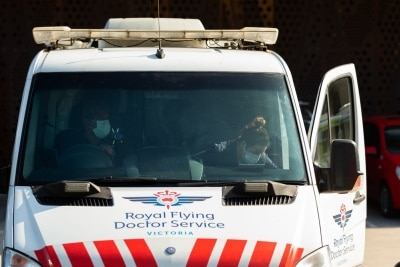 """MELBOURNE, AUSTRALIA - JULY 29: A Royal Flying Doctor crew arrive at Epping Gardens Aged Care Facility as authorities rush to evacuate residents by ambulance during COVID 19 on 29 July, 2020 in Melbourne, Australia. Staff at the Epping Gardens Aged Care facility, where there have been 83 COVID-19 cases and five deaths, have been stood down over an """"extremely dangerous breach"""". A memo was sent to relatives by management to advise that police had been called after it emerged that staff had held a get-together on the property. This comes as 295 new Coronavirus cases were discovered overnight, bringing the states total active cases to 4,775. (Photo by Speed Media/Icon Sportswire)"""