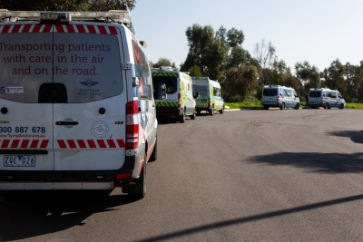 """MELBOURNE, AUSTRALIA - JULY 29: Patient transport vehicles line up outside of the Epping Gardens Aged Care Facility as authorities rush to evacuate residents by ambulance during COVID 19 on 29 July, 2020 in Melbourne, Australia. Staff at the Epping Gardens Aged Care facility, where there have been 83 COVID-19 cases and five deaths, have been stood down over an """"extremely dangerous breach"""". A memo was sent to relatives by management to advise that police had been called after it emerged that staff had held a get-together on the property. This comes as 295 new Coronavirus cases were discovered overnight, bringing the states total active cases to 4,775. (Photo by Speed Media/Icon Sportswire)"""