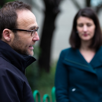 MELBOURNE, AUSTRALIA - JULY 5: The Federal Greens Leader Adam Bandt (L)speaks to the media with the Victorian Deputy Leader Ellen Sandell looking on (R) at the entrance of 12 Sutton Street North Melbourne after a failed attempt to drop multi lingual leaflets into the the mailboxes of residents in that tower to help them understand why they were forbidden to leave their units amid a full and total lockdown of 9 housing commission high rise towers in North Melbourne and Flemington during COVID 19 on 5 July, 2020 in Melbourne, Australia. After 108 new cases where uncovered overnight, the Premier Daniel Andrews announced on July 4 that effective at midnight last night, two more suburbs have been added to the suburb by suburb lockdown being Flemington and North Melbourne. Further to that, nine high rise public housing buildings in these suburbs have been placed under hard lockdown for a minimum of five days, effective immediately.  Residents in these towers will not be allowed to leave their units for any reason. Police will be stationed at every entry and exit point, every level, and they will also surround these locations preventing any movement in, or out. There is a total of 1354 units and over 3000 residents living in these buildings including the states most vulnerable people. Authorities will ensure that food, medical supplies and general supplies will be provided as well as any mental health services as required. This move is unprecedented in Australia's history and will require an unprecedented number of police to enforce the total lockdown with estimates of over 500 police officers stationed at these locations to enforce the lockdown orders. This comes amid fears of a second wave of Coronavirus infections in Victoria, with the total active cases now being 509. Fourteen are linked to controlled out breaks, 25 from routine testing and 69 are still under investigation. These new restrictions will remain in place for fourteen days with fears of further lockdowns to