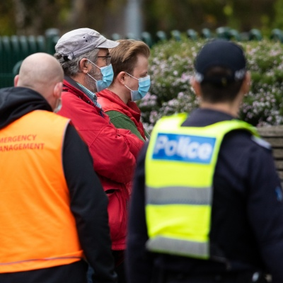 MELBOURNE, AUSTRALIA - JULY 5: Government workers gather out side of  120 Racecourse Road amid a full and total lockdown of 9 housing commission high rise towers in North Melbourne and Flemington during COVID 19 on 5 July, 2020 in Melbourne, Australia. After 108 new cases where uncovered overnight, the Premier Daniel Andrews announced on July 4 that effective at midnight last night, two more suburbs have been added to the suburb by suburb lockdown being Flemington and North Melbourne. Further to that, nine high rise public housing buildings in these suburbs have been placed under hard lockdown for a minimum of five days, effective immediately.  Residents in these towers will not be allowed to leave their units for any reason. Police will be stationed at every entry and exit point, every level, and they will also surround these locations preventing any movement in, or out. There is a total of 1354 units and over 3000 residents living in these buildings including the states most vulnerable people. Authorities will ensure that food, medical supplies and general supplies will be provided as well as any mental health services as required. This move is unprecedented in Australia's history and will require an unprecedented number of police to enforce the total lockdown with estimates of over 500 police officers stationed at these locations to enforce the lockdown orders. This comes amid fears of a second wave of Coronavirus infections in Victoria, with the total active cases now being 509. Fourteen are linked to controlled out breaks, 25 from routine testing and 69 are still under investigation. These new restrictions will remain in place for fourteen days with fears of further lockdowns to come. The Government have stressed that if Victorians do not follow the basic COVIDSafe rules, the whole state will go back in to lockdown. (Photo by Speed Media/Icon Sportswire)