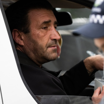 MELBOURNE, AUSTRALIA - JULY 5: A man is seen showing his ID to police as he enters 120 Racecourse Road amid a full and total lockdown of 9 housing commission high rise towers in North Melbourne and Flemington during COVID 19 on 5 July, 2020 in Melbourne, Australia. After 108 new cases where uncovered overnight, the Premier Daniel Andrews announced on July 4 that effective at midnight last night, two more suburbs have been added to the suburb by suburb lockdown being Flemington and North Melbourne. Further to that, nine high rise public housing buildings in these suburbs have been placed under hard lockdown for a minimum of five days, effective immediately.  Residents in these towers will not be allowed to leave their units for any reason. Police will be stationed at every entry and exit point, every level, and they will also surround these locations preventing any movement in, or out. There is a total of 1354 units and over 3000 residents living in these buildings including the states most vulnerable people. Authorities will ensure that food, medical supplies and general supplies will be provided as well as any mental health services as required. This move is unprecedented in Australia's history and will require an unprecedented number of police to enforce the total lockdown with estimates of over 500 police officers stationed at these locations to enforce the lockdown orders. This comes amid fears of a second wave of Coronavirus infections in Victoria, with the total active cases now being 509. Fourteen are linked to controlled out breaks, 25 from routine testing and 69 are still under investigation. These new restrictions will remain in place for fourteen days with fears of further lockdowns to come. The Government have stressed that if Victorians do not follow the basic COVIDSafe rules, the whole state will go back in to lockdown. (Photo by Speed Media/Icon Sportswire)