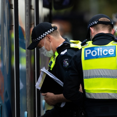 MELBOURNE, AUSTRALIA - JULY 5: Police officers step into a mobile operations bus parked at 120 Racecourse Road amid a full and total lockdown of 9 housing commission high rise towers in North Melbourne and Flemington during COVID 19 on 5 July, 2020 in Melbourne, Australia. After 108 new cases where uncovered overnight, the Premier Daniel Andrews announced on July 4 that effective at midnight last night, two more suburbs have been added to the suburb by suburb lockdown being Flemington and North Melbourne. Further to that, nine high rise public housing buildings in these suburbs have been placed under hard lockdown for a minimum of five days, effective immediately.  Residents in these towers will not be allowed to leave their units for any reason. Police will be stationed at every entry and exit point, every level, and they will also surround these locations preventing any movement in, or out. There is a total of 1354 units and over 3000 residents living in these buildings including the states most vulnerable people. Authorities will ensure that food, medical supplies and general supplies will be provided as well as any mental health services as required. This move is unprecedented in Australia's history and will require an unprecedented number of police to enforce the total lockdown with estimates of over 500 police officers stationed at these locations to enforce the lockdown orders. This comes amid fears of a second wave of Coronavirus infections in Victoria, with the total active cases now being 509. Fourteen are linked to controlled out breaks, 25 from routine testing and 69 are still under investigation. These new restrictions will remain in place for fourteen days with fears of further lockdowns to come. The Government have stressed that if Victorians do not follow the basic COVIDSafe rules, the whole state will go back in to lockdown. (Photo by Speed Media/Icon Sportswire)