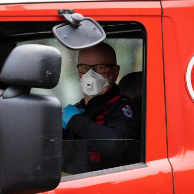 MELBOURNE, AUSTRALIA - JULY 5: Fire crews wearing facemasks are seen driving away from the Flemington housing commission tower amid a full and total lockdown of 9 housing commission high rise towers in North Melbourne and Flemington during COVID 19 on 5 July, 2020 in Melbourne, Australia. After 108 new cases where uncovered overnight, the Premier Daniel Andrews announced on July 4 that effective at midnight last night, two more suburbs have been added to the suburb by suburb lockdown being Flemington and North Melbourne. Further to that, nine high rise public housing buildings in these suburbs have been placed under hard lockdown for a minimum of five days, effective immediately.  Residents in these towers will not be allowed to leave their units for any reason. Police will be stationed at every entry and exit point, every level, and they will also surround these locations preventing any movement in, or out. There is a total of 1354 units and over 3000 residents living in these buildings including the states most vulnerable people. Authorities will ensure that food, medical supplies and general supplies will be provided as well as any mental health services as required. This move is unprecedented in Australia's history and will require an unprecedented number of police to enforce the total lockdown with estimates of over 500 police officers stationed at these locations to enforce the lockdown orders. This comes amid fears of a second wave of Coronavirus infections in Victoria, with the total active cases now being 509. Fourteen are linked to controlled out breaks, 25 from routine testing and 69 are still under investigation. These new restrictions will remain in place for fourteen days with fears of further lockdowns to come. The Government have stressed that if Victorians do not follow the basic COVIDSafe rules, the whole state will go back in to lockdown. (Photo by Speed Media/Icon Sportswire)