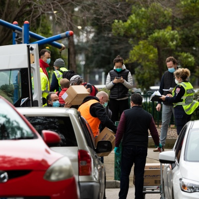 MELBOURNE, AUSTRALIA - JULY 5: Government workers gather out side of  120 Racecourse Road as boxes of PPE are loaded on to a a trolley amid a full and total lockdown of 9 housing commission high rise towers in North Melbourne and Flemington during COVID 19 on 5 July, 2020 in Melbourne, Australia. After 108 new cases where uncovered overnight, the Premier Daniel Andrews announced on July 4 that effective at midnight last night, two more suburbs have been added to the suburb by suburb lockdown being Flemington and North Melbourne. Further to that, nine high rise public housing buildings in these suburbs have been placed under hard lockdown for a minimum of five days, effective immediately.  Residents in these towers will not be allowed to leave their units for any reason. Police will be stationed at every entry and exit point, every level, and they will also surround these locations preventing any movement in, or out. There is a total of 1354 units and over 3000 residents living in these buildings including the states most vulnerable people. Authorities will ensure that food, medical supplies and general supplies will be provided as well as any mental health services as required. This move is unprecedented in Australia's history and will require an unprecedented number of police to enforce the total lockdown with estimates of over 500 police officers stationed at these locations to enforce the lockdown orders. This comes amid fears of a second wave of Coronavirus infections in Victoria, with the total active cases now being 509. Fourteen are linked to controlled out breaks, 25 from routine testing and 69 are still under investigation. These new restrictions will remain in place for fourteen days with fears of further lockdowns to come. The Government have stressed that if Victorians do not follow the basic COVIDSafe rules, the whole state will go back in to lockdown. (Photo by Speed Media/Icon Sportswire)