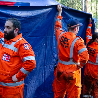 SES personnel hold up a tarpaulin where William Callaghan was receiving medical attention at Mt Disappointment in Victoria. An air-and-ground search is continuing for lost Victorian teenager William Callaghan, who suffers from non-verbal autism and is lost in steep and rugged terrain in Victoria after temperatures dropped below freezing overnight.